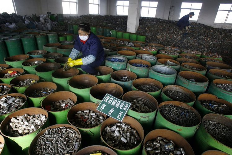 Workers sort batteries at an electronic waste recycling factory in Wuhan